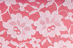 White lace on pink. White textured lace on a pink background Stock Photo