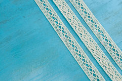 White lace ribbons on blue wooden background. Stock Photo