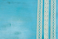 White lace ribbons on blue wooden background. Royalty Free Stock Image