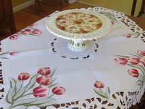 A white lace table cloth with a beautiful red tulip print. This beautiful lace table cloth adorned with a red tulip print was bought in Belgium. It is supporting Royalty Free Stock Image