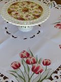 A white lace table cloth with a beautiful red tulip print. This beautiful lace table cloth adorned with a red tulip print was bought in Belgium. It is supporting Stock Images