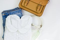 White lace women`s blouse, blue jeans, a brown handbag and a white belt on a white background. Women`s casual outfits. Flat lay, stock photo