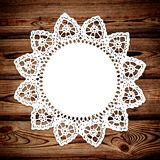 White lace on wooden background. Beautiful white lace of home manufacture in the form of a circular swipe is on a dark wooden background. There is a place for stock photography