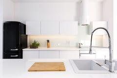 White, lacquer kitchen and black retro fridge. Cozy, white, lacquer kitchen in modern house with black retro fridge Royalty Free Stock Photo