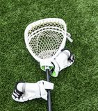 Lacrosse goalie stick with hgloves on turf field. A white lacrosse goalie stick is lying on a green turf field with white gloves attached stock image