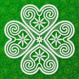 White lacy clover in Russian Vologda lace style on green doodles background Stock Image