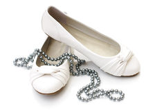 White ladies shoes with silver pearl necklace. On white background Royalty Free Stock Photography