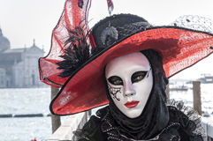 White lady with a red hat in Venice. Traditional mask at Venice Carnival royalty free stock image
