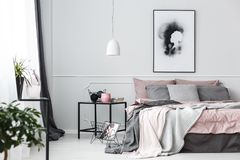 Poster in pink bedroom interior. White lamp above table next to the bed against a wall with poster in pink bedroom interior stock images