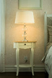 White lamp on bedside wooden table Stock Photo