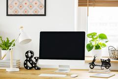 White lamp next to computer desktop on wooden desk in home office interior with plant. Real photo stock photography