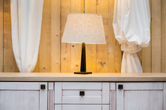 White lamp on the warderobe with raw wooden wall Royalty Free Stock Photography