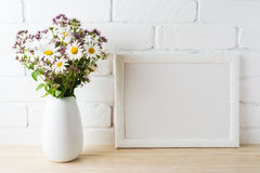 White landscape frame mockup with blooming wildflower bouquet in. White landscape frame mockup with blooming wildflower s bouquet in styled vase near painted Royalty Free Stock Images