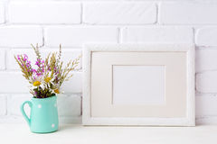 White landscape frame mockup with chamomile and purple flowers i Stock Photo