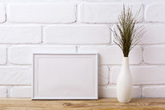 White landscape frame mockup with dark grass in elegant vase royalty free stock image