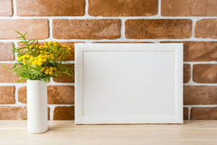 White landscape frame mockup with yellow flowers near exposed br Stock Photography