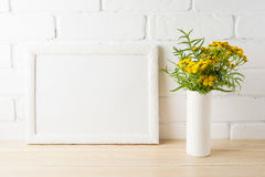 White landscape frame mockup with yellow flowers near painted br Royalty Free Stock Images