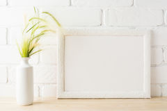 White landscape frame mockup with yellow and green wild grass ea stock image
