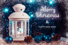 White lantern with a burning candle and ornament on the background of the Christmas tree with lights. Beautiful stock photo