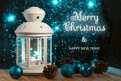 White lantern with a burning candle and ornament on the background of the Christmas tree with lights. Beautiful stock images