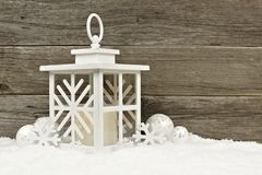White lantern with Christmas baubles in snow against wood Royalty Free Stock Photography