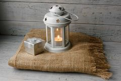 White lantern with a lighted candle next to a gift box. White lantern with a lighted candle inside on a brown tablecloth. Candlestick with decorative stars Royalty Free Stock Photography
