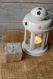 White lantern with a lighted candle next to a gift box. White lantern with a lighted candle inside on a brown tablecloth. Candlestick with decorative stars Royalty Free Stock Images