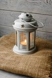 White lantern with a lighted candle next to a gift box. White lantern with a lighted candle inside on a brown tablecloth. Candlestick with decorative stars Royalty Free Stock Photos