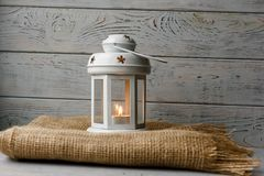 White lantern with a lighted candle next to a gift box. White lantern with a lighted candle inside on a brown tablecloth. Candlestick with decorative stars Stock Photo