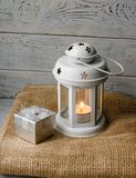 White lantern with a lighted candle next to a gift box. White lantern with a lighted candle inside on a brown tablecloth. Candlestick with decorative stars Royalty Free Stock Image