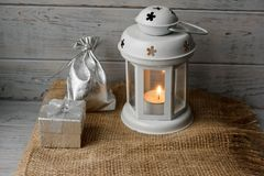 White lantern with a lighted candle next to a gift box. White lantern with a lighted candle inside on a brown tablecloth. Candlestick with decorative stars Royalty Free Stock Photo