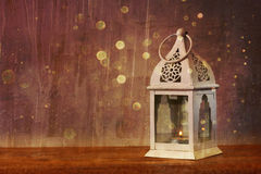 White lantern over wooden table and glitter lights background Royalty Free Stock Photos