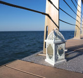 White lantern on the sea pier in the evening Stock Image