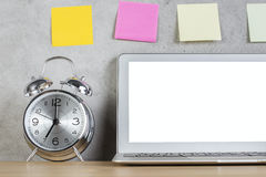White laptop, alarm and stickers Royalty Free Stock Photo