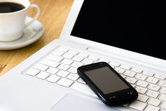 White laptop and coffee cup. White laptop, black cell phone and cup of coffee arranged on wooden table Stock Photo