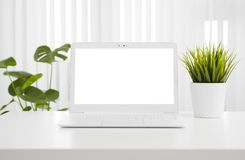 White laptop computer mockup with blank screen on office table Royalty Free Stock Images