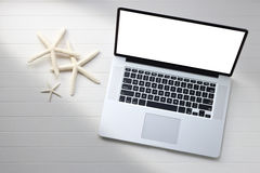 White Laptop Computer. A still life with a laptop computer and starfish on a white background Royalty Free Stock Images