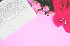 White laptop computer with woman accessories and pink roses on pink background, Lifestyle concept Royalty Free Stock Image