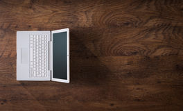 White laptop on a dark wooden desktop Stock Photos