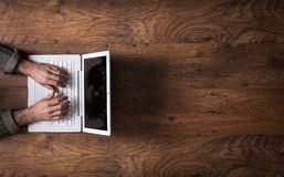 White laptop on a dark wooden desktop. Male hands working on a white laptop on a wooden desktop and copy space at right Royalty Free Stock Photography