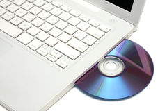 White laptop with dvd disk in slot isolated. White laptop with violet-blue color dvd disk in slot-loading drive Royalty Free Stock Photo