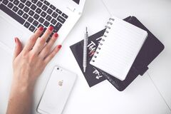 White laptop, female hand, note, pen, phone, desk Royalty Free Stock Images