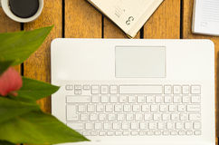 White laptop, notepad and coffee cup as seen from above sitting on wooden surface.  stock image