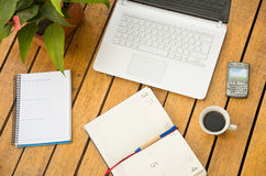 White laptop, notepad, coffee cup and mobile phone as seen from above sitting on wooden surface Stock Photo