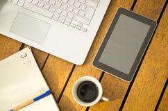 White laptop, notepad, coffee cup and tablet as seen from above sitting on wooden surface.  stock photo