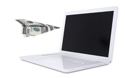 White laptop and the plane of dollars Stock Image
