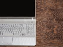 White laptop is standing on a wooden table. stock photography
