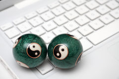 White laptop with yin yang balls on a keyboard. Royalty Free Stock Photography