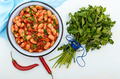 White large beans in sweet and sour tomato sauce in a bowl on a light background. Stock Photo