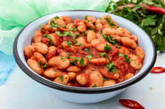 White large beans in sweet and sour tomato sauce in a bowl on a light background. Royalty Free Stock Photography